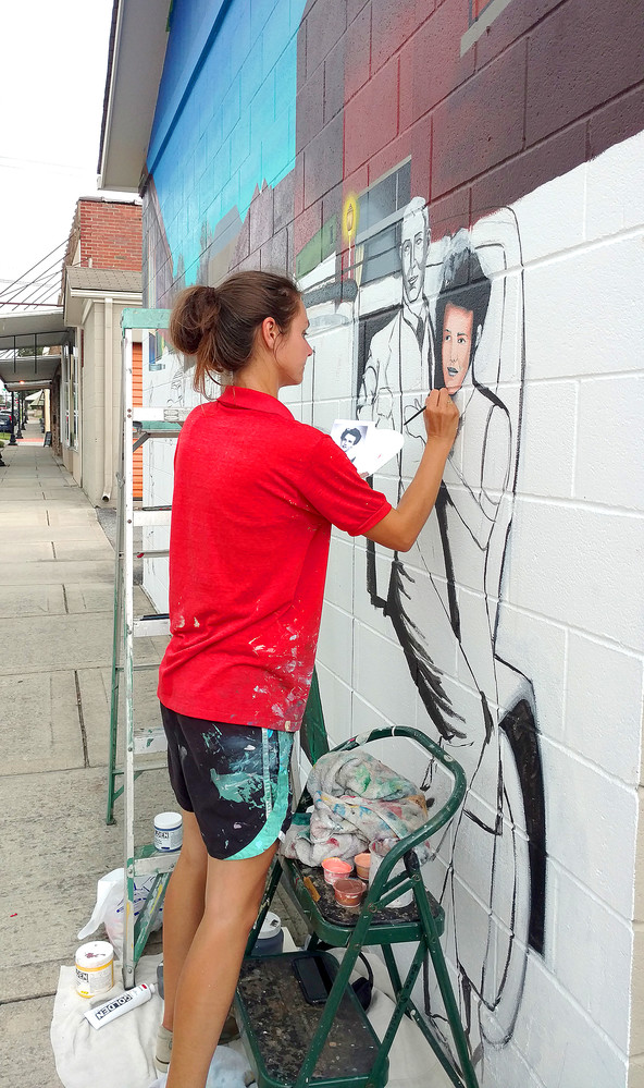 "Muralist Erica Swensen paints a scene from 1937 Broad Street on the Gaw storage building facing Cedar Avenue. Swenson said the mural is set at twilight so most details are visible, but the street lights are lit, giving passerbys a ""night out on the town"" feeling. The project is funded by WestSide businesses and more donations can be made by dropping them off at Father Tom's Pub."