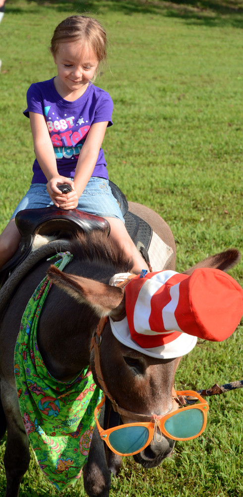 "Tailynn Short, 4, rides on ""Ricky"" the donkey from Maynard and Sons Petting Zoo as part of JAKES Day at Mustard Seed Ranch on Saturday."