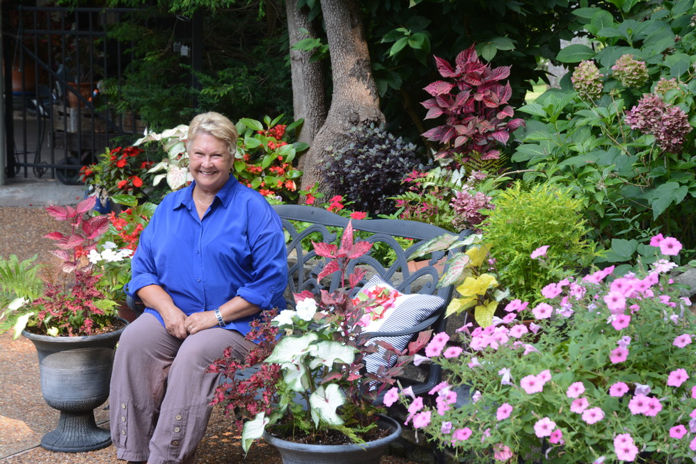 Master Gardener sits in a shady area of her gardens.
