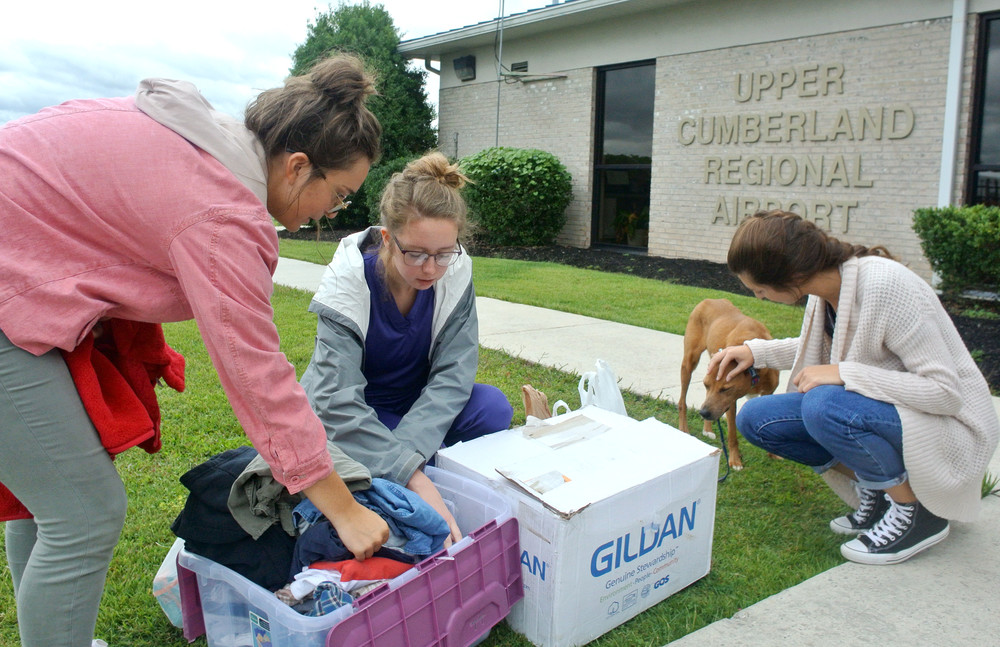 Volunteers go through supplies donated to Hurricane Irma evacuees. From left are Lauren Clark, Ally Jackson, whose father piloted the evacuation plane, and Delaney Ethridge, consoling Cookie, a dog who survived the ordeal.