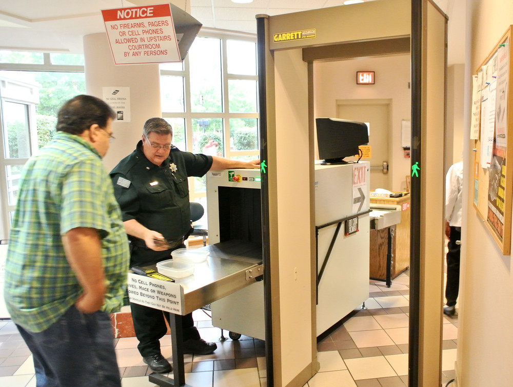 Sheriffs deputy Tim Gothard operates the metal detector at the Putnam County Justice Center.