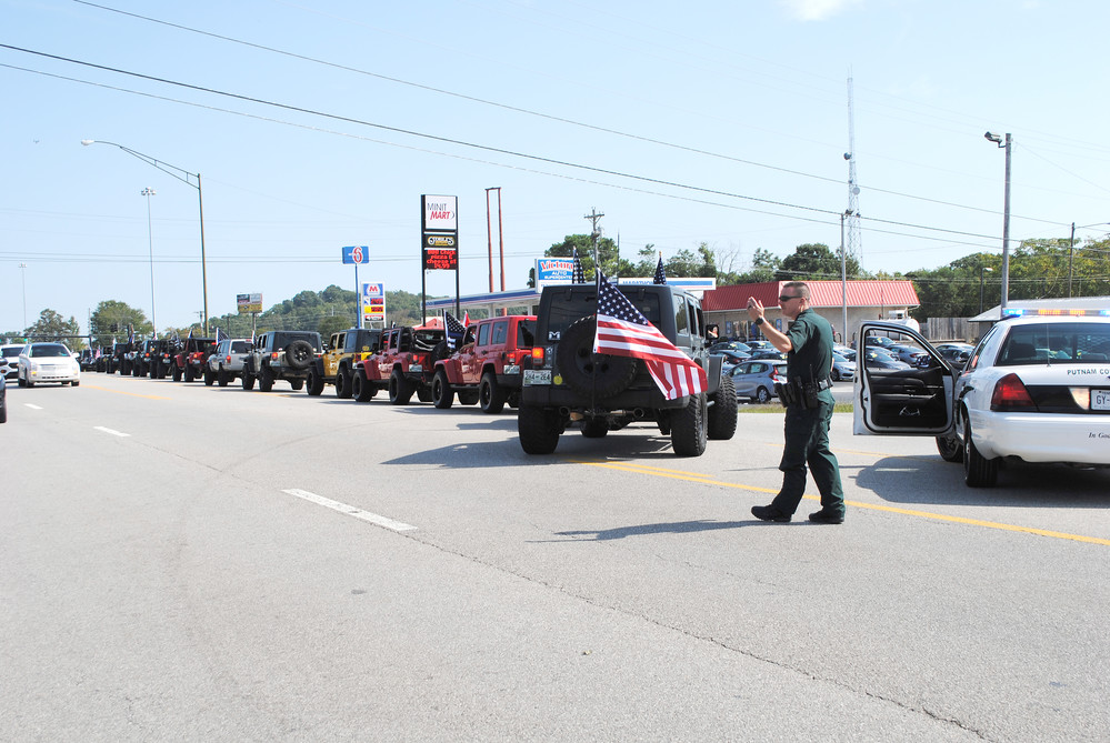 Putnam County Sheriff's Deputy Cris Crannigan waves the Jeeps onto Jefferson as people took part in the annual Jerry Dale Abston Memorial Ride Saturday morning.