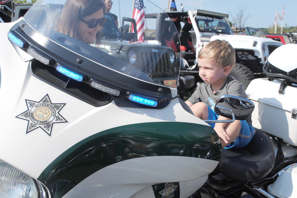 Two-year-old Mace Parker tries out a Putnam County Sheriff's Department motorcycle next to his mother, Jessica, during the ride in honor of the late Jerry Dale Abston.