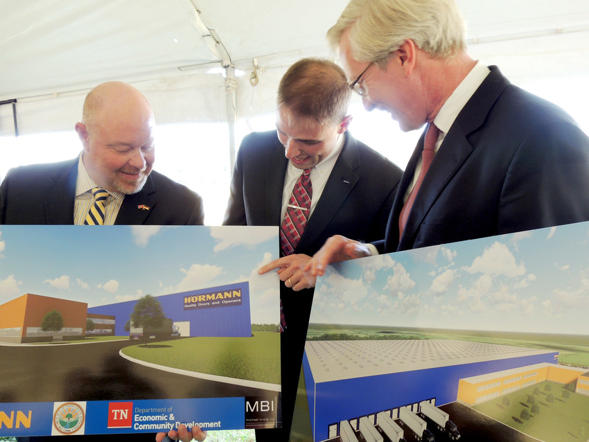 Denny Wayne Robinson, left, White County executive, looks over the renderings of the new facility with Camron Rudd, president of North American operations for Hormann; and Christoph Hormann, managing partner.