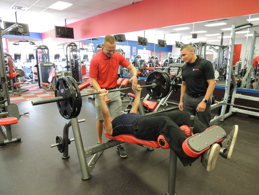 EJ Williams, left, and Jerry Pugh, co-owners of Workout Anytime, helps Devon Borges on the weight bench.