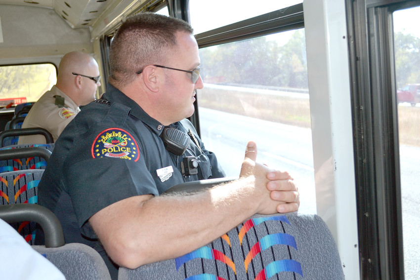 Cookeville Police Officer Greg Young, in front, and THP Trooper Craig Wilkerson look for distracted drivers while riding a THP bus Wednesday.
