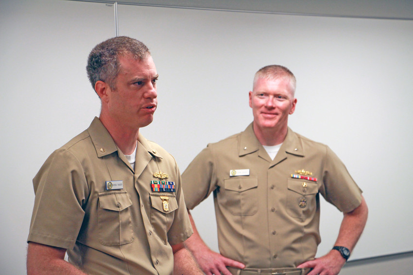 LCDR Derek Rader, left, speaks at the Aug. 30 ceremony where he was pinned with the Distinguished Pistol Shot Badge as Adm. John Wade looks on.