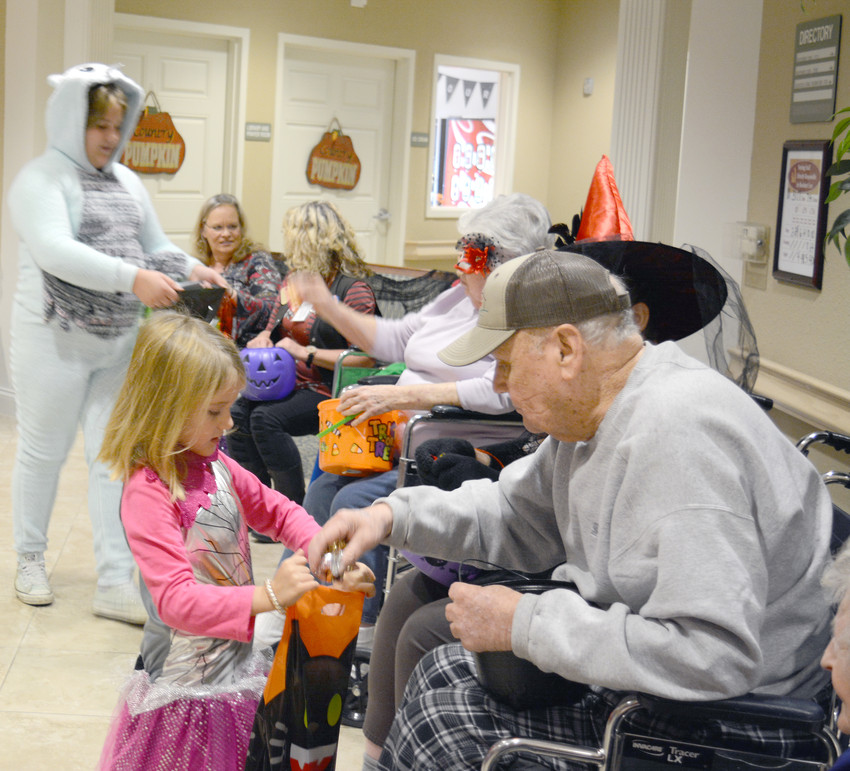 Residents at Life Care Center of Sparta welcomed local children for Trick-or-Treat Tuesday evening. Here Bill Hickey puts some candy in Autumn Lewis' bag.