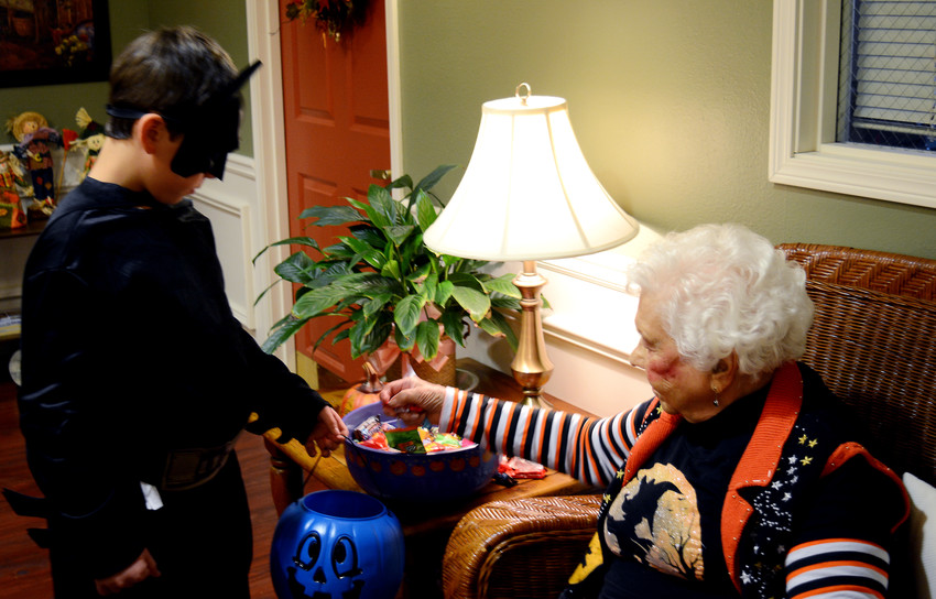 When Alfred isn't around, Batman needs a helping hand. Life Care of Sparta resident Opal Haston, 95, helps Batman, 8-year-old Dryston Howard, choose some candy.