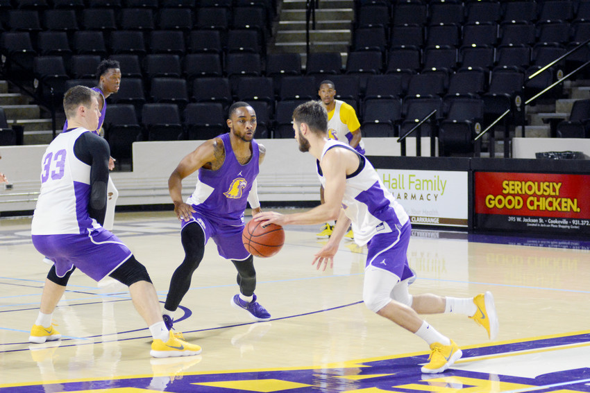 Graduate student Kajon Mack, center, tries to avoid a screen during a recent practice as he defends senior guard Aleksa Jugovic, right. The Golden Eagles open the regular season tonight with visiting Midway University.