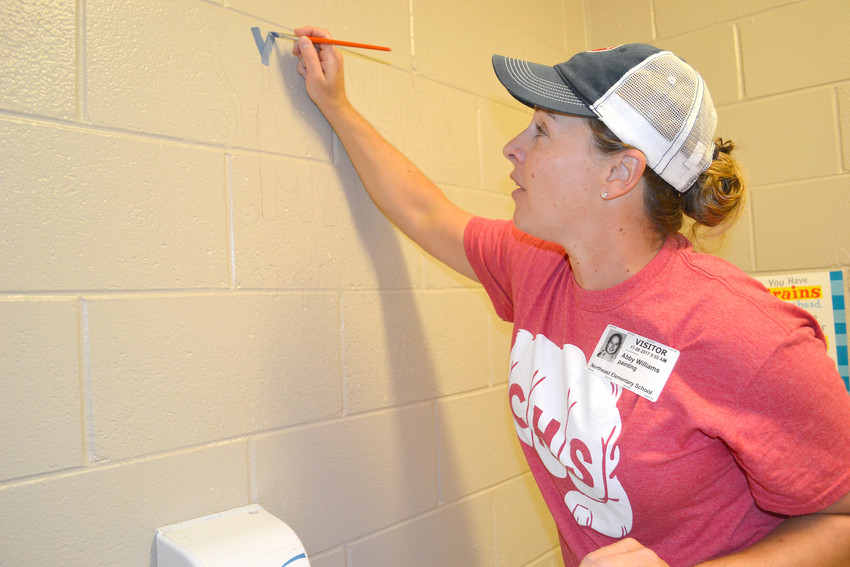 Walls of Worth organizer Abby Williams prepares to paint an uplifting sentiment on a wall at Northeast Elementary School.