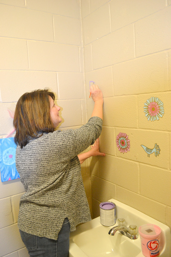 Taryn Bolton of Collegeside Church of Christ, one of the adopters of Northeast Elementary School, helps out with painting.