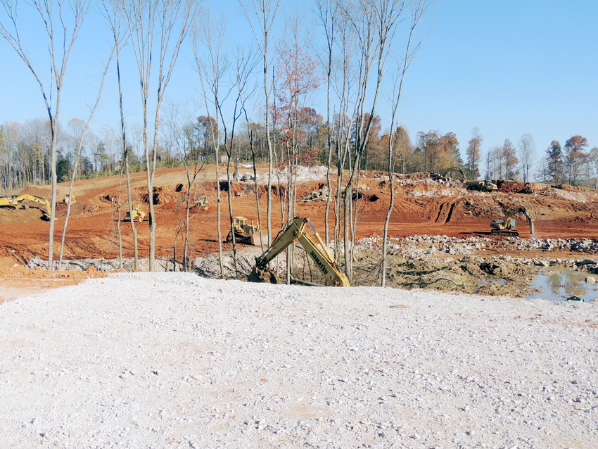 Contractors work to clear and level the land that the Shoppes at Eagle Point will be developed on.