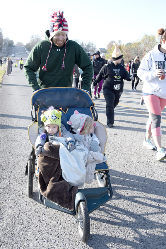 Josiah and Adaline Olsen take the easy way around the Turkey Trot course, being pushed by their dad, Jacob.