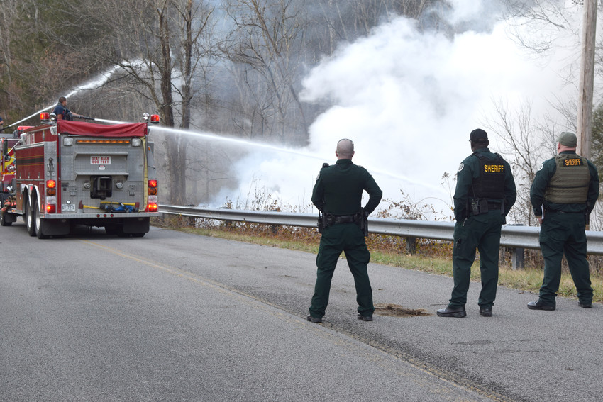 A Putnam County firefighter shoots water onto the remains of an abandoned Silver Point home destroyed by fire Saturday afternoon while deputies with the Putnam County Sheriff's Office stand by.