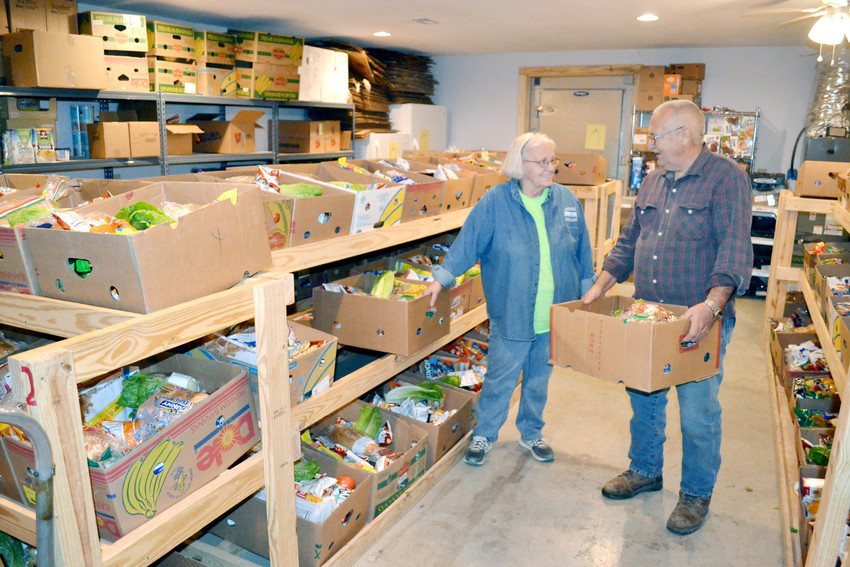 Patty and Doyle Howard of Vine Ridge Missionary Baptist Church prepare to distribute boxes of food from the church's food pantry program.