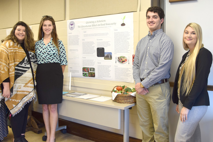 "Sara Hampton, Hannah Crouch, Hadley Krantz and Shelby Merritt with their project, ""Growing a Solution: The Greenhouse Effect on Food Insecurity."""