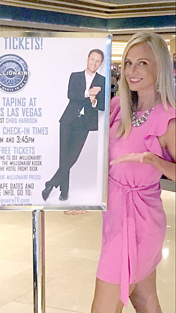 "Lisa Little poses next to a poster advertising the taping of ""Who Wants To Be A Millionaire"" in August. Episodes featuring Little will air next week."