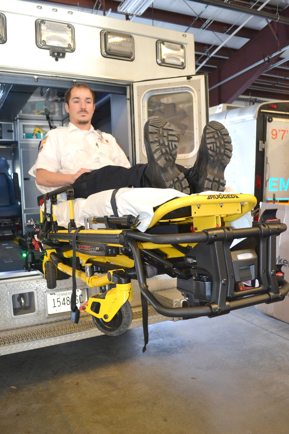 Johnathan Price sits on a cot attached to a Power load system purchased with a federal grant.