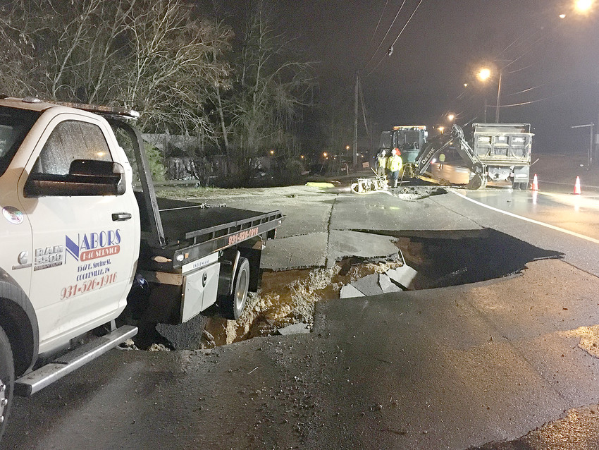 A Nabors tow truck was the temporary victim of a road that washed away when a 14-inch water line broke Monday night on Highway 70.