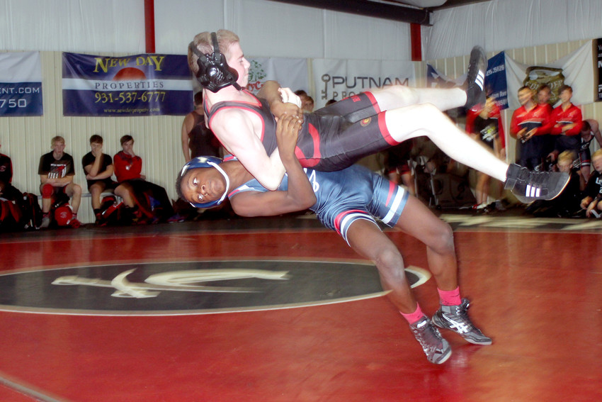 Cookeville's Derico Jimerson slams a Coffee County wrestler during the Cavs' 74-6 win on Thursday night at CHS.
