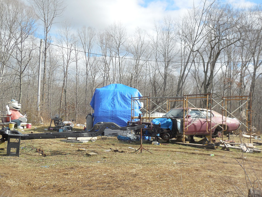 A tarp covers a trailer and an inoperable car sits on property in western Putnam County that officials have cited for code violations.