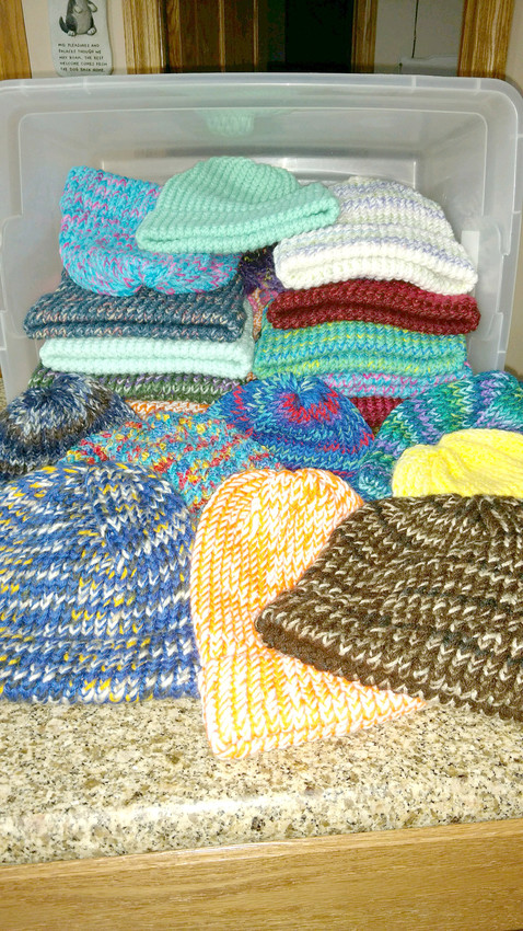 A storage container of knitted hats Dorene McManus made while watching television in the evenings.