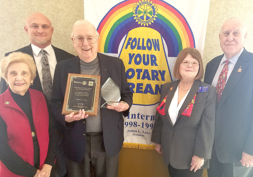 "On hand Wednesday for the awards presentations, from left, Claudine and James Lacy with current Rotary Club President Jerry Boyd, District Governor Deborah Davis and Past R.I. President John Germ. The group is standing in front of Lacy's 1998-99 Rotary International Banner, which features the theme, ""Follow Your Rotary Dream."""