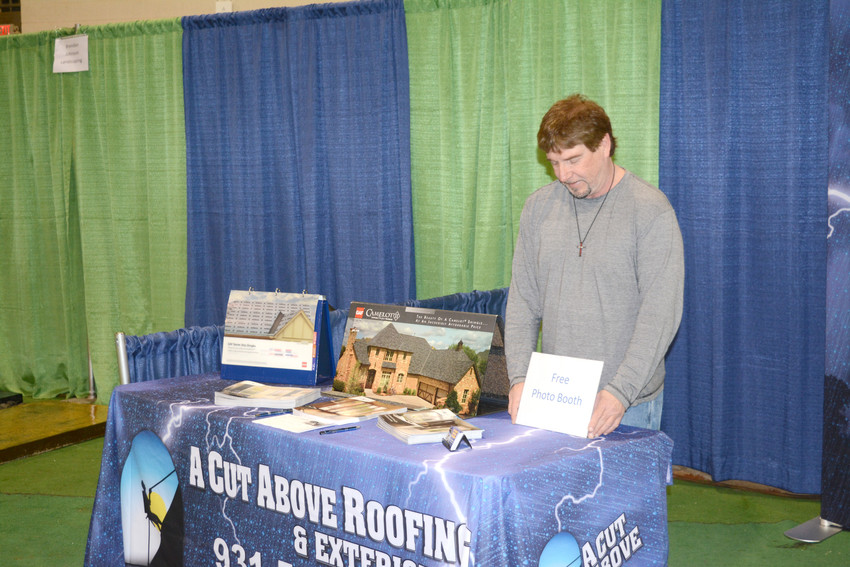 Robert Smith with A Cut Above Roofing is standing at his booth to place a sign for free photos.