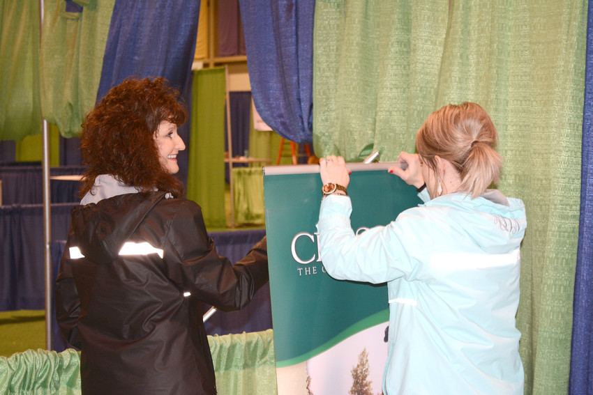 Nancy Wilson, left, and Ashley DeRossett, right, are working together to put their Cumberland County Chamber of Commerce booth up.