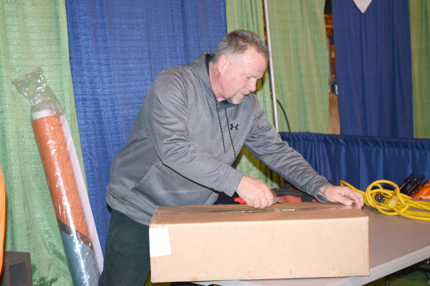 Dave Boender with Cove Generators opens a box to set up his booth.