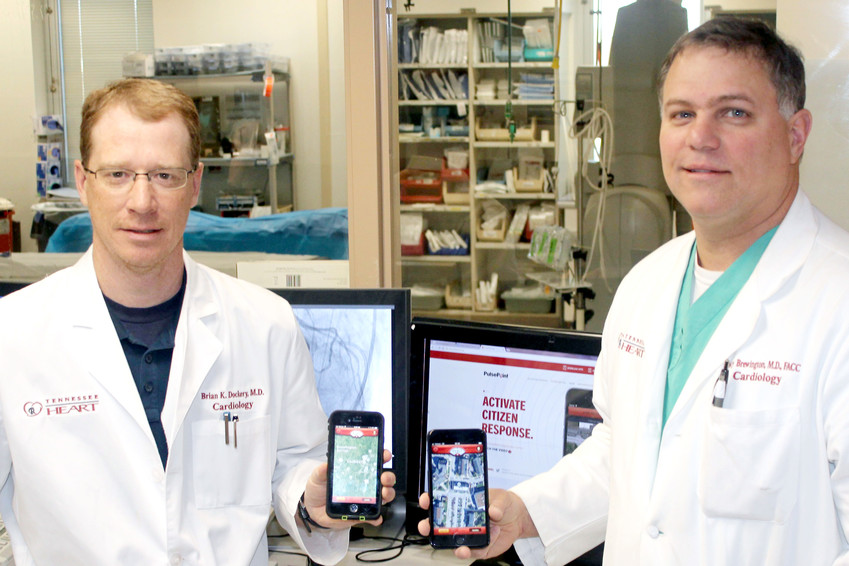 Cardiologists Dr. Brian Dockery, left, and Dr. Stacy Brewington, both of Tennessee Heart, hold up their phones with the Pulsepoint app.