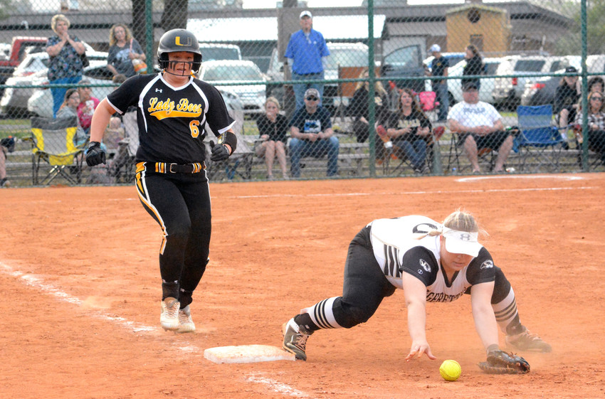 Upperman's Sam Greenwood, left, dashes for a base while a DeKalb County infielder fumbles with the ball during a game in Smithville on Tuesday