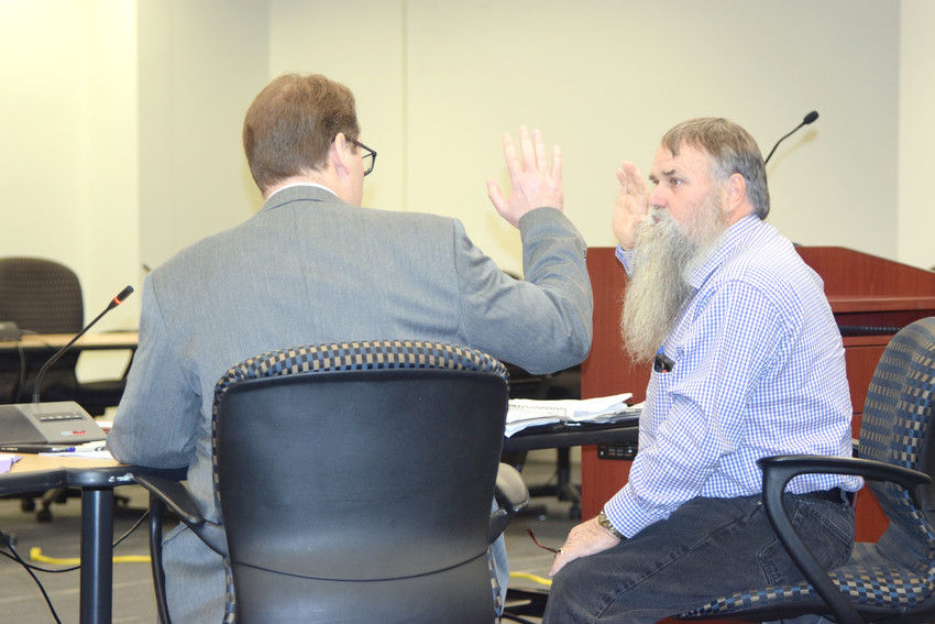 Former Putnam Election Commissioner Terry Herrin, right, is sworn in by Tennessee Coordinator of Elections Mark Goins, left, during a hearing to remove Herrin as an election commissioner Monday for offensive, sexual comments Herrin allegedly made in the presence of election office staff.