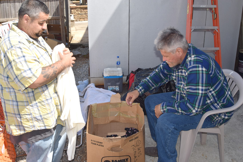 T.J., left, and Jeffrey Lee Bates, right, sort through donated clothes at the Cookeville Rescue Mission.