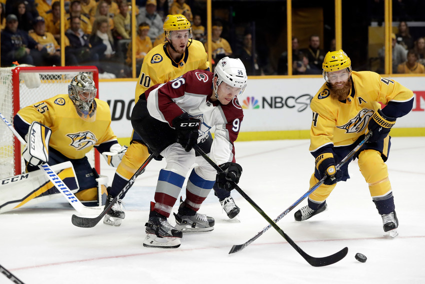 Colorado Avalanche right wing Mikko Rantanen (96), of Finland, passes the puck in front of Nashville Predators center Colton Sissons (10) and defenseman Ryan Ellis (4) during the first period in Game 2 of an NHL hockey first-round playoff series Saturday, April 14, 2018, in Nashville, Tenn. (AP Photo/Mark Humphrey)