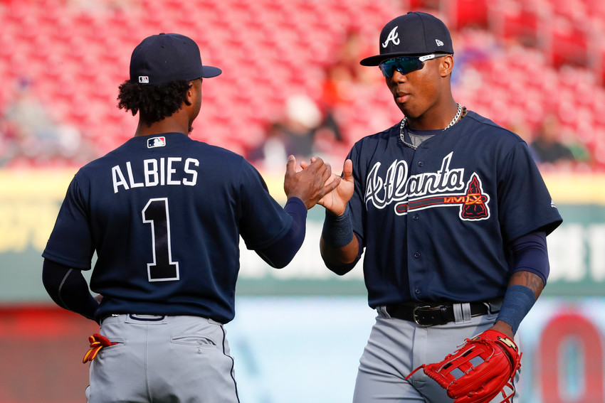 Atlanta Braves center fielder Ronald Acuna Jr., right, and second baseman Ozzie Albies (1) meet on the field as the Braves warmed up for a baseball game against the Cincinnati Reds, Wednesday, April 25, 2018, in Cincinnati. (AP Photo/John Minchillo)