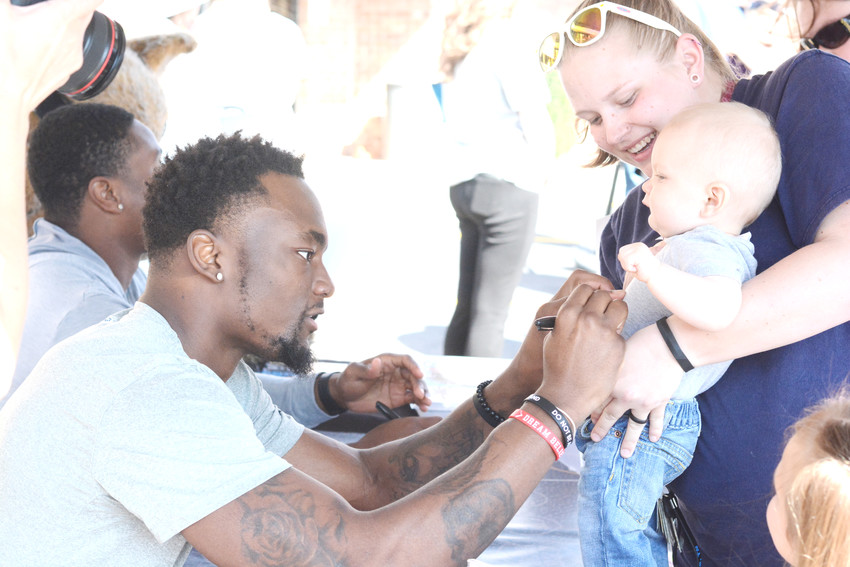 Tennessee Titans' Corey Davis, left, signs a baby during the Titans Caravan stop in Monterey on Saturday.