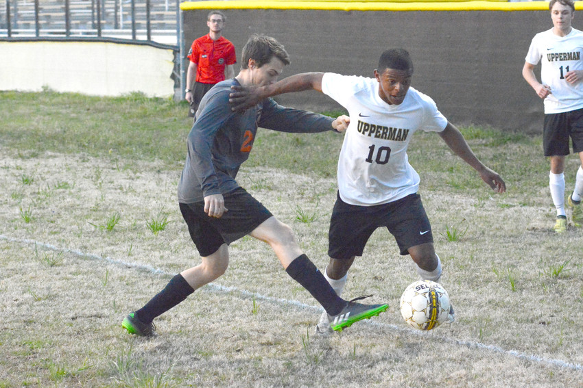 Teyo Rodriguez, above right, tries to dribble around a Cascade player during soccer action Friday night. The match ended in a2-2 tie.