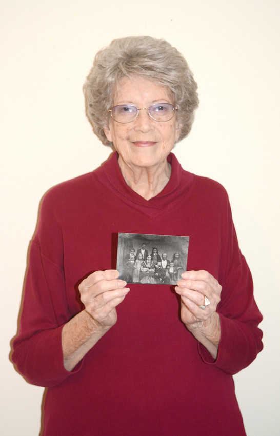 Sue Gentry Burgess enjoys looking back on her childhood. She is holding a photo of her great-grandfather and his family.
