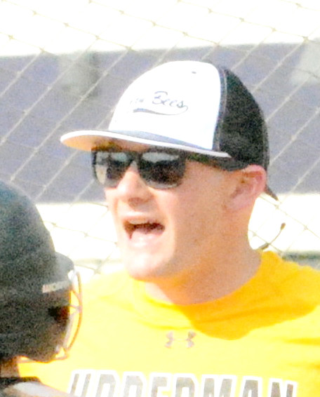 Upperman High School Softball Coach Dustin Williams talks to his players during a break in the game.