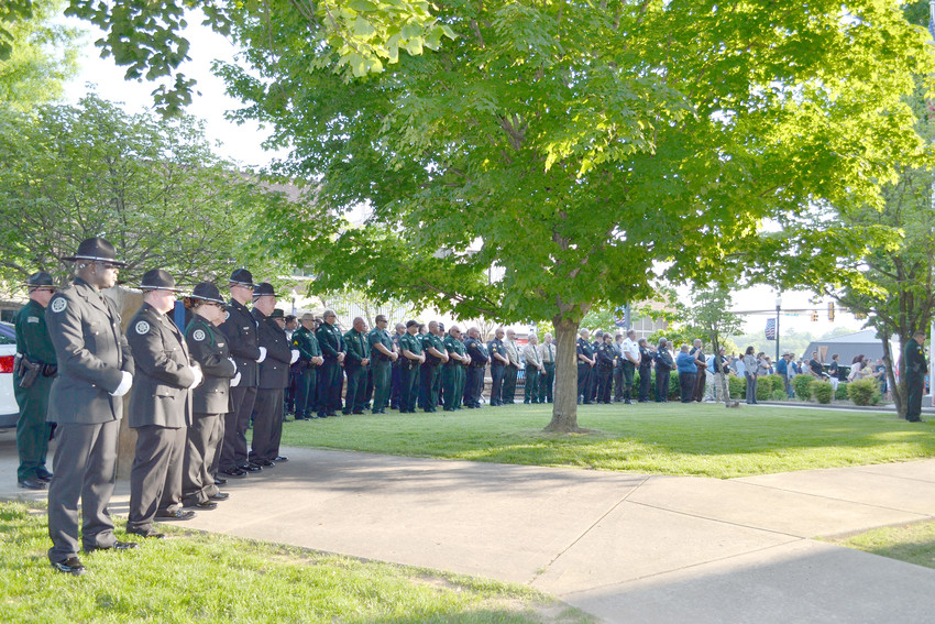 Deputies and officials from the Putnam County Sheriff's Office gather on the lawn of the Putnam County Courthouse Monday evening to remember law enforcement officers who perished while serving their communities.
