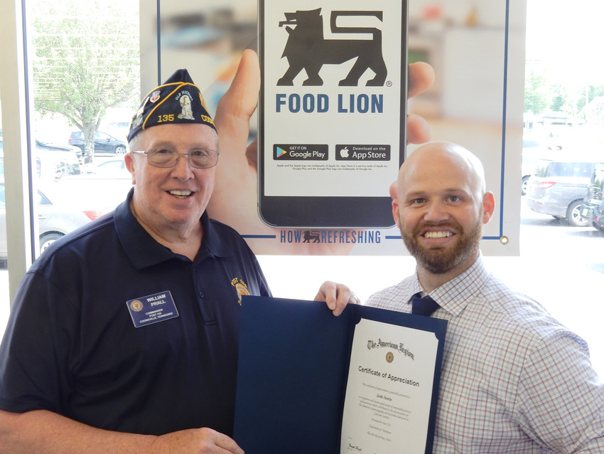 Commander Bill Prall of American Legion Post 135 in Cookeville presents a certificate of appreciation to Spring Street Food Lion Manager Joshua Storie for his assistance in coordinating and providing more than 4,000 bottles of water for veterans and visitors to The Wall That Heals in April. Storie's Spring Street store as well as the Jackson Street Food Lion provided the donation to the Wall's three-day stop in Cookeville, which saw more than 30,000 visitors.