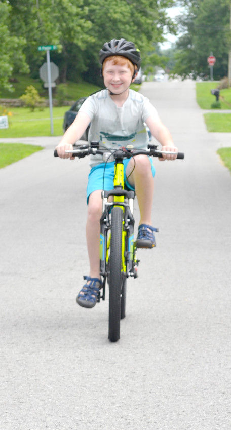 Asher Wiggins rides his bike down a residential street in Monterey.