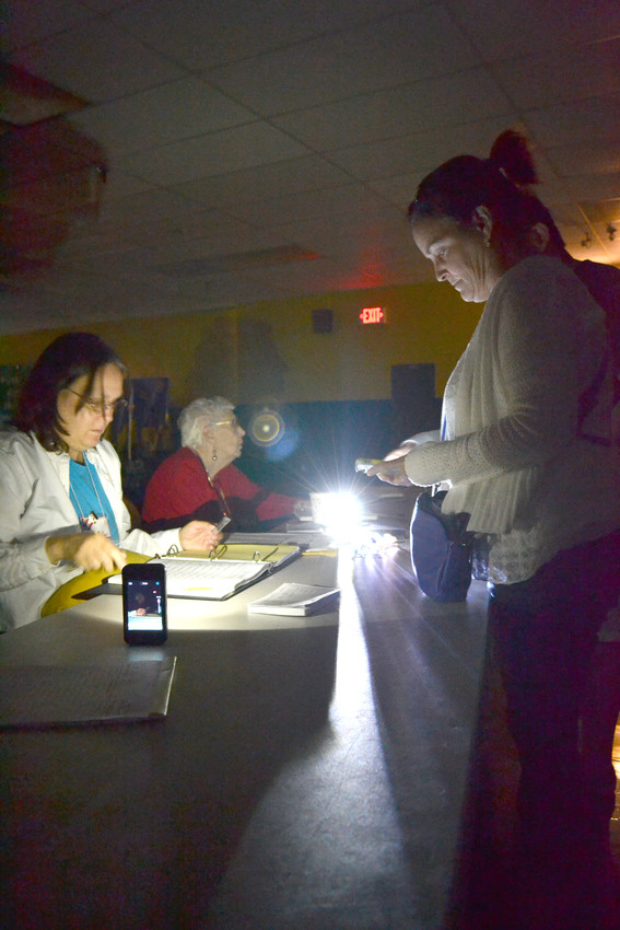 Cookeville voter Seanad Chang, right, and election worker Gloria Miller use lights from cell phones to fill out paperwork after a brief power outage at the Northeast Elementary School precinct as the polls opened Thursday.