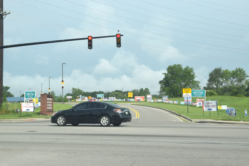A car passes by dozens of campaign signs on County Services Drive in July prior to the August election.