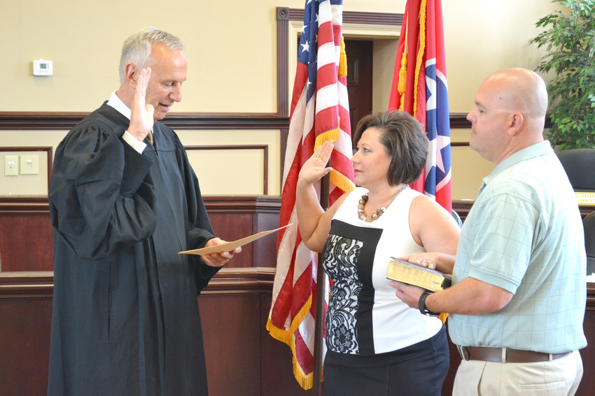 New Circuit Court Clerk Jennifer Wilkerson, center, with her husband Craig at her side, is sworn into office by Judge David Patterson.
