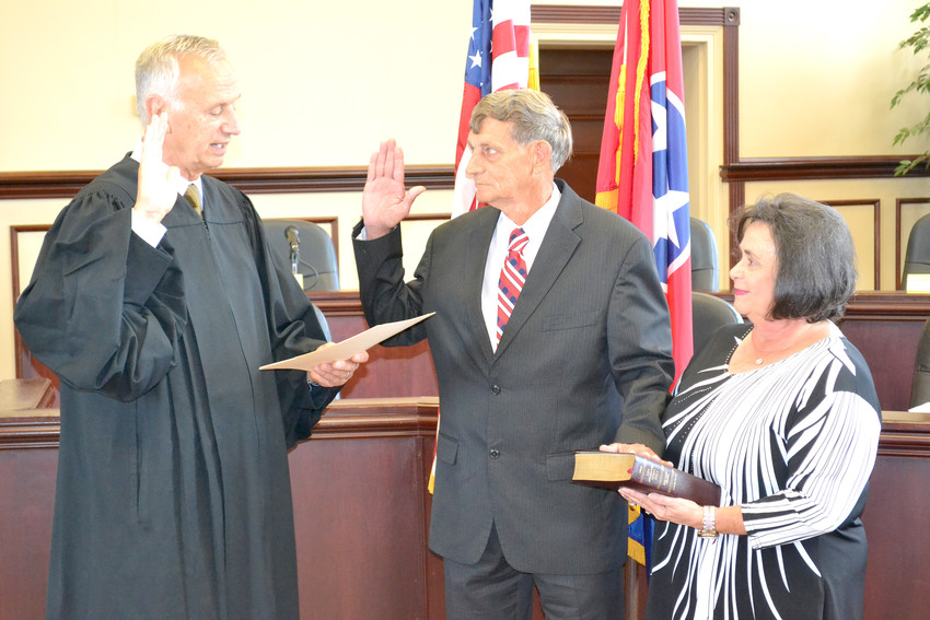 Kathy Nelson, right, holds the Bible for her husband, Freddie Nelson, as he is sworn in by Judge David Patterson.