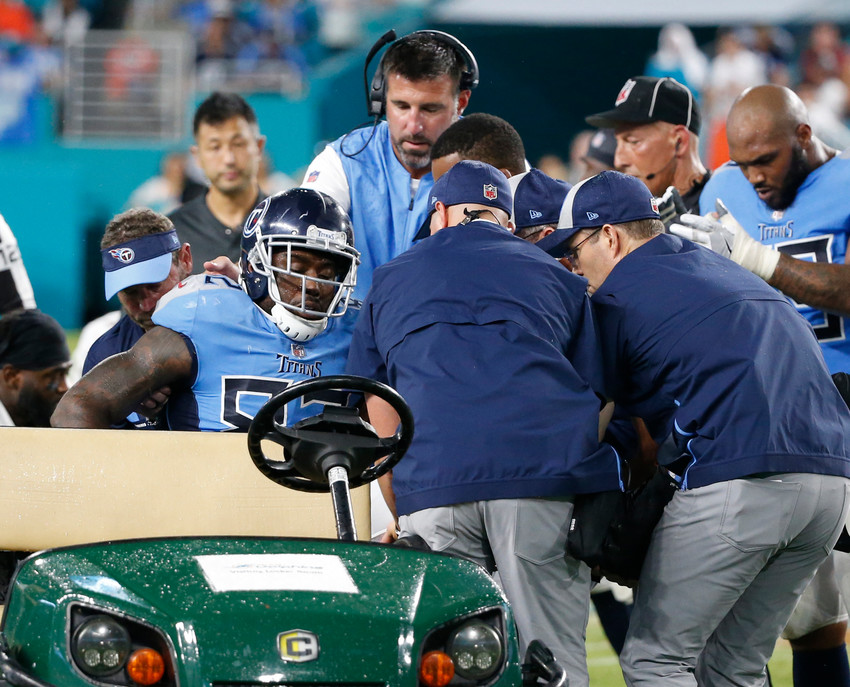 Tennessee Titans tight end Delanie Walker (82) is assisted on to a cart by the head coach Mike Vrabel and members of the Titans staff, after he was injured on a play, during the second half of a game against the Miami Dolphins, Sunday, in Miami Gardens, Fla.