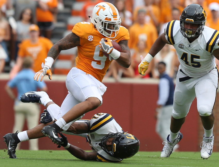 Tennessee running back Tim Jordan (9) runs the ball as East Tennessee State University linebacker Jared Folks (31) and defensive lineman Nasir Player (45) chase after him during a game Saturday in Knoxville.